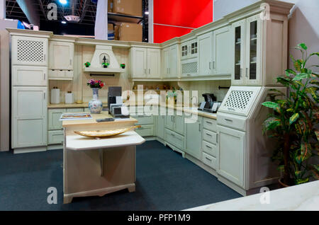 A modern kitchen with white wooden furniture in an exhibition. - Stock Photo