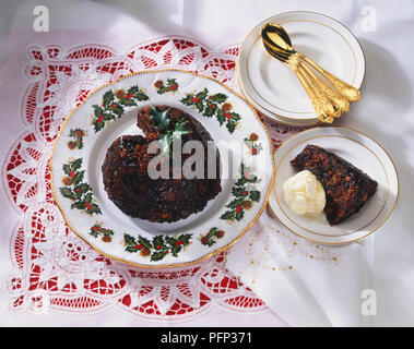 Christmas Pudding, served on dinner plate decorated with holly leaves and berries, and side plate with brandy butter, accompanied by gold dessert spoons - Stock Photo