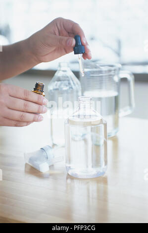 Making all-purpose surface cleaner, adding eucalyptus oil to glass bottle containing vinegar and water, using pipette, close-up - Stock Photo
