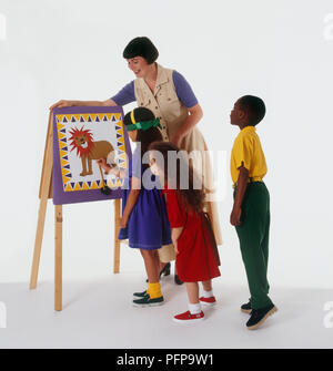 Adult supervising children playing pin the tail on the lion - Stock Photo