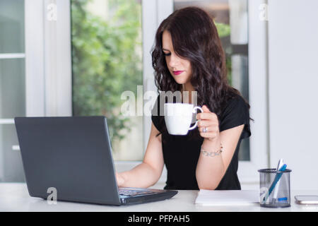 Beautiful young girl working on laptop at office desk and drinking cup of coffee. Modern business and job concept. Close up, selective focus - Stock Photo