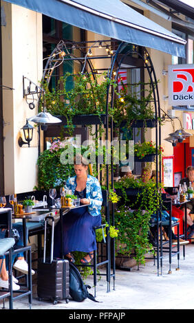 Woman sitting outside of a cafe in Sofo, Sodermalm, Stockholm, Sweden - Stock Photo