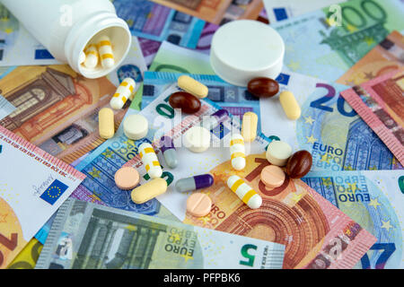 Different pills and capsules on background of different euro bills - Stock Photo
