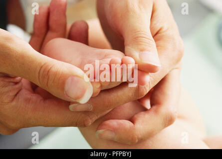 Woman's hands holding babys bare foot, close up. - Stock Photo