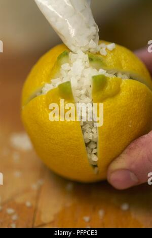 Preserving lemons, filling a cut lemon with salt - Stock Photo