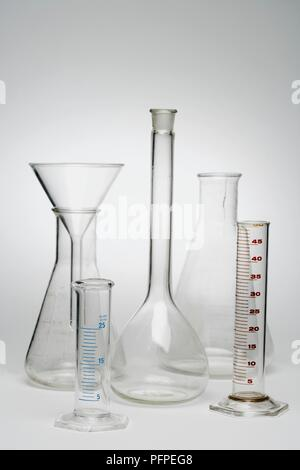 Various glass beakers, measuring tubes, funnel - Stock Photo