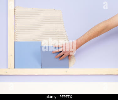 Hand placing tile on wall with adhesive - Stock Photo