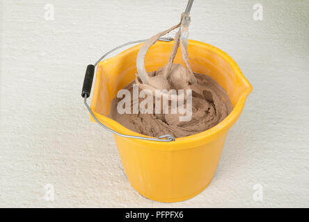Electric stirrer in bucket of plaster - Stock Photo