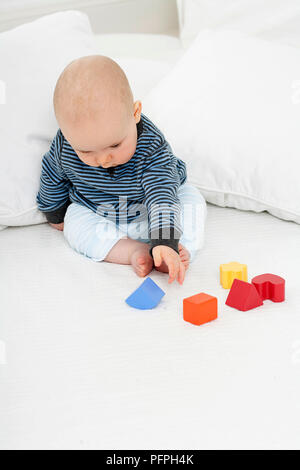 Baby boy sitting on bed propped up by cushions playing with plastic toy shapes - Stock Photo