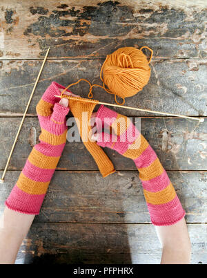 Teenage girl with arm warmers on holding a piece of knitting, wood background - Stock Photo