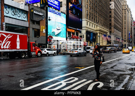 New York City, USA - June 21, 2018: Black woman trying to get a taxi while talking on the phone a rainy day in Manhattan. - Stock Photo
