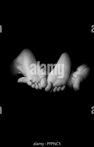 Newborn Baby Feet Supported by Mothers Hand on Black Background - Stock Photo