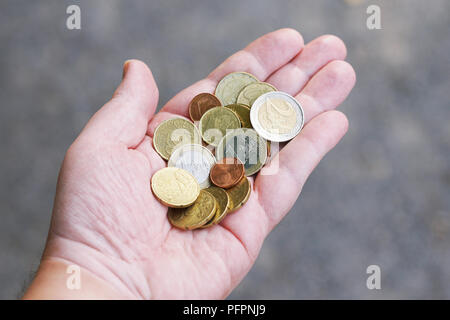 handful of small loose pocket change euro cent coins in palm of hand, money finance currency concept - Stock Photo