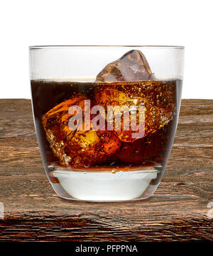 Cola with cognac or rom in rocks glass on wooden table - Stock Photo