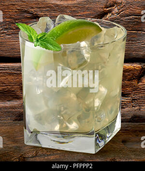 Vodka lime, gimlet, caipirinha or gin tonic with ice in glass on wooden background - Stock Photo