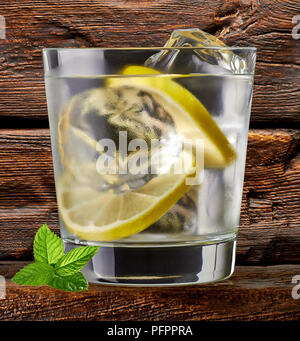 Gin tonic, vodka or rum with lime wedges on wooden table and background - Stock Photo