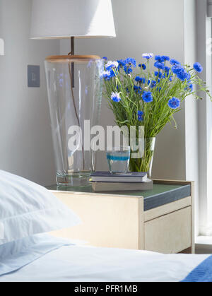 Electric Lamp Vase Of Blue Flowers And Glass Of Water On Stack Of