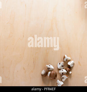 Chestnut mushrooms whole and quartered, on wooden surface - Stock Photo