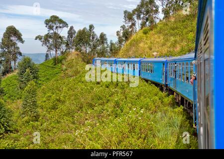 Sri Lanka, Central Province, Nuwara Eliya, train passing through mountains - Stock Photo