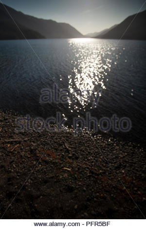 Sun setting between mountains over Lake Crescent at dusk, Olympic National Park, WA USA - Stock Photo