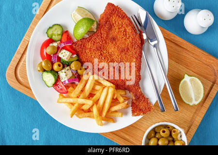 crispy fried flounder in breadcrumbs served with fresh vegetables, feta, olives greek salad and french fries on a white plate with silver fork and kni - Stock Photo