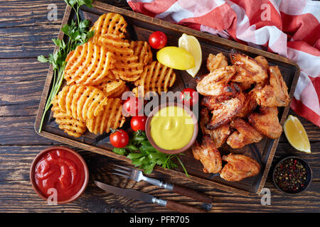 fried chicken wings, Crispy Potato Criss Cross Fries on a clay plates on a wooden table with mustard and tomato sauce dipping, view from above, close- - Stock Photo
