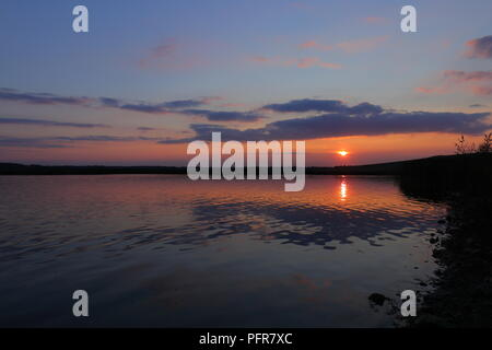 Calm water reflections of the sun setting over RSPB St Aidan's Nature Park between Leeds & Castleford - Stock Photo