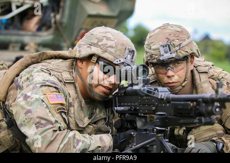 Spc. Jhon Sandoval (left), and Spc. Evgenig Famenev (right), infantrymen assigned to1st Squadron, 2nd Cavalry Regiment, search for enemy troops during the Bull Run V training exercise with Battle Group Poland inOlecko, Poland, onMay 22, 2018. Battle Group Poland is a unique, multinational coalition of U.S., U.K., Croatian and Romanian Soldiers who serve with the Polish 15th Mechanized Brigade as a deterrence force in support of NATO's Enhanced Forward Presence. - Stock Photo