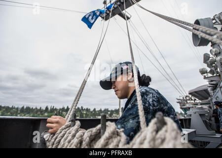 "Wash. (May 25, 2018) Airman Macey Zuniga, from Mililani Town, Hawaii, raises the ""12th Man"" flag aboard the aircraft carrier USS John C. Stennis (CVN 74). The Seattle Seahawks football team and Sea Gals cheerleaders held a military appreciation event aboard John C. Stennis to meet and visit with Sailors. John C. Stennis is pier-side after returning to homeport after the completion of a seven-week underway where the ship's crew completed TSTA/FEP early and Carrier Strike Group 3 Group Sail in preparation for its next scheduled deployment. - Stock Photo"