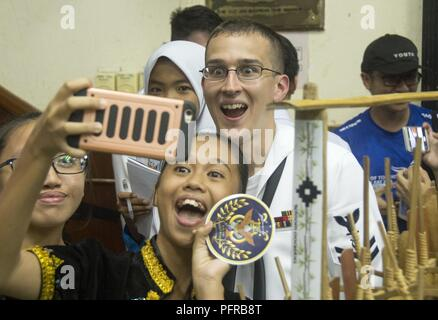 KOTA KINABALU, MALAYSIA (May 25, 2018) Musician 2nd Class Holden Moyer of the U.S. 7th Fleet Bandtakes a photo with a member of the SMK Tamparuli bamboo orchestra after a performance at SMK Tamparuli High School  in Kota Kinabalu, Malaysia. The band is supporting a U.S. 7th Fleet theater security cooperation mission and will be traveling to several Indo-Pacific countries in the coming weeks. - Stock Photo