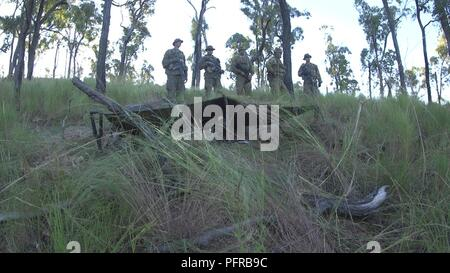 U.S. Marines and Australian Defence Force members observe the defenses prior to a night attack during Ex-Warfighter on Shoal Water Bay Training Area, Australia May 23, 2018. Ex-Warfighter is an exercise apart of Marine Rotational Darwin that integrated Company F as an attachment to 2-14 Queensland Mounted Infantry. - Stock Photo