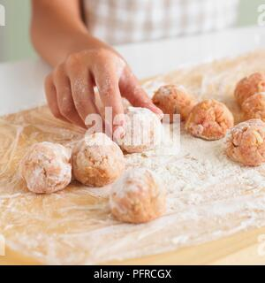 Child rolling meatballs in flour on wooden chopping board - Stock Photo