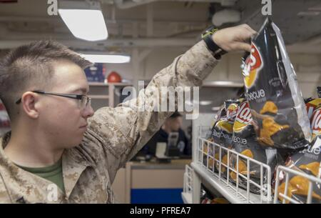 MEDITERRANEAN SEA (May 23, 2018) U.S. Marine Lance Cpl. Axel Gonzalez, from Chicago, and assigned to the Battalion Landing Team of the 26th Marine Expeditionary Unit, restocks shelves in the ship's store aboard the San Antonio-class amphibious transport dock ship USS New York (LPD 21) May 23, 2018. New York, homeported in Mayport, Florida, is conducting naval operations in the U.S. 6th Fleet area of operations in support of U.S. national security interest in Europe and Africa. - Stock Photo