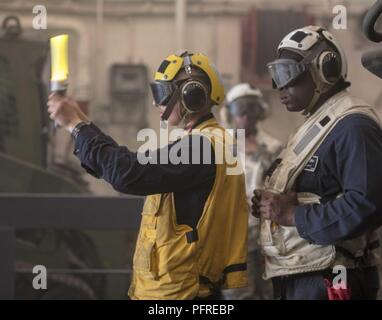 MEDITERRANEAN SEA (May 24, 2018) Boatswain's Mate 2nd Class Bennie Lott, from Dallas, right, stands safety watch for Seaman Connor Morford, from Puyallup, Washington, as he directs a landing craft, air cushion out of the well deck of the San Antonio-class amphibious transport dock ship USS New York (LPD 21) May 24, 2018. New York, homeported in Mayport, Florida, is conducting naval operations in the U.S. 6th Fleet area of operations in support of U.S. national security interest in Europe and Africa. - Stock Photo