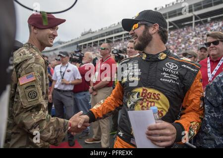 A Soldier from Fort Bragg, North Carolina, shakes the hand of Martin Truex Jr., NASCAR driver, during the pre-race events of the Coca-Cola 600 on May 27, 2018, at Charlotte Motor Speedway in Concord, North Carolina. Several NASCAR drivers introduced service members to the crowd before the race. - Stock Photo