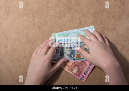 Hand holding American dollar  banknotes isolated on wooden background - Stock Photo