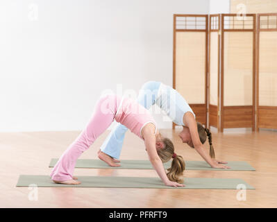 two children doing downward dog yoga pose stock photo