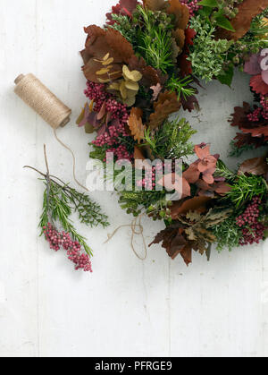 Foliage, dyed flowers and berry wreath with string and stems on table - Stock Photo