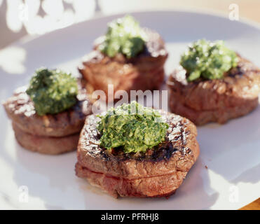 Chargrilled fillet steak with salsa verde served on white plate, close-up - Stock Photo
