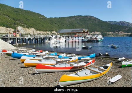 Argentina, San Martin de Los Andes, Lago Lacar, canoes and boats on the beach and in the lake - Stock Photo