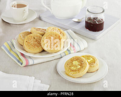Crumpets on plates, some with butter on, and jar of jam and tea cup in background - Stock Photo
