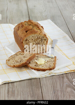Banana and walnut bread, loaf and buttered slices - Stock Photo