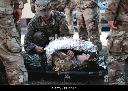 Pfc. Grant Granath (left) and Pfc. Jakob Willams (right), infantrymen assigned to1st Squadron, 2nd Cavalry Regiment, practice preparing a casualty for evacuation during combat lifesaver training withBattle Group Poland at Bemowo Piskie Training Area, Poland,May 30, 2018. Battle Group Poland is a unique, multinational coalition of U.S., U.K., Croatian and Romanian Soldiers who serve with the Polish 15th Mechanized Brigade as a deterrence force in support of NATO's Enhanced Forward Presence. - Stock Photo