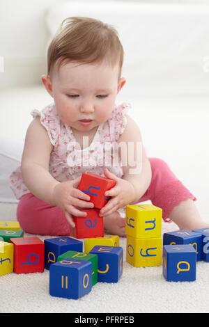 Baby girl (8.5 months) playing with wooden blocks with letters and numbers on - Stock Photo