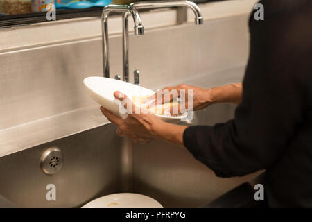 Woman washing the dishes in kitchen sink - Stock Photo