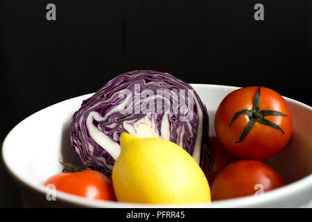 Red cabbage cut in half in white bowl with lemon and tomato isol - Stock Photo