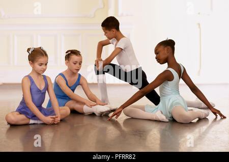 ballet dancers doing stretching exercises group of young