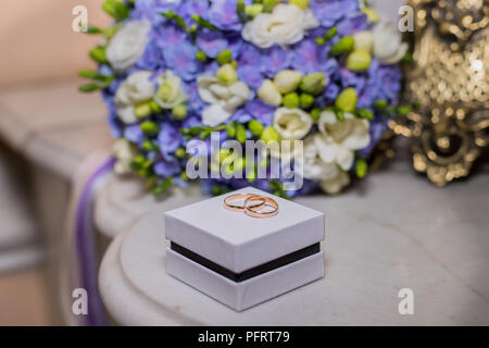 wedding rings lie on white box on a beautiful bouquet background, as bridal accessories.solemn event, festive event, wedding day. Pair of golden rings. - Stock Photo