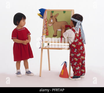Two toddlers playing pin the tail on the donkey - Stock Photo