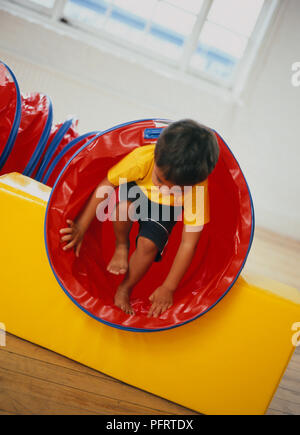 Barefoot toddler wearing yellow T-shirt and black shorts climbing out of plastic tunnel - Stock Photo